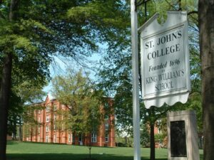 """ST. JOHN'S COLLEGE FOUNDED 1696 KING WILLIAM'S SCHOOL"" in black lettering on white decorative sign on white sign post in between two trees with overarching green-leafed branches and trees in the background; black iron memorial plaque/statue on off-white cement block underneath sign; on green grassy field with two brick buildings in the distance; has white-framed windows and stands against blue sky"
