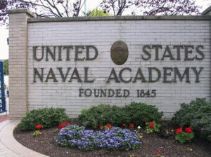 """UNITED STATES NAVAL ACADEMY FOUNDED 1845"" in bronze lettering with oval seat between ""UNITED"" and ""STATES""' on white brick wall with tree behind it and greyish sky; green bushes and bushes with red and purple flowers in front on brown mulch and white brick pathway in the bottom left corner"
