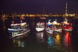 Six boats lined up on the water in (from left to right) blue, green, brown, blue, yellow and red paint with white bottoms; other sailboats behind them and the lit-up Annapolis downtown on the far shore against night sky