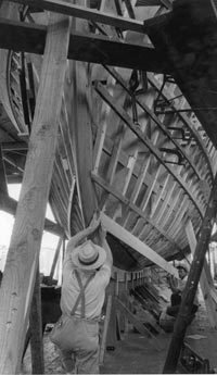 black and white image of man in suspenders and brimmed hat working on the skeleton of Trumpy yacht with framework of boat propped up on supports being helped by another man in the background