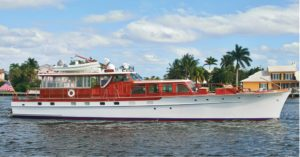 Trumpy yacht (brown and white) on blue water with green trees in the background, building with white roof and light blue sky with puffy white clouds