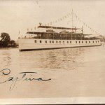 sepia artistic image of trumpy yacht decorated with flags on water with trees on the right side and solid sky in the background, signature in blueish ink on bottom left corner