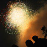 multicolored fireworks against black sky with orangey colored smoke that outlines the silhouette of three people watching the show and a stray tree branch with leaves