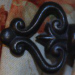 black wrought-iron ornamental piece in the shape of a heart with decorative curls on red and white background