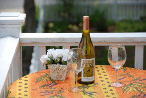 two wine glasses, Great Frogs white wine, and white flowers in ceramic vase on dark-and-light orange striped table cloth decorated with purple and yellow flowers that have green stems and leaves with white railing behind it and blurred green garden in the background surrounded by white picket fence