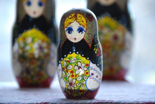 trio of painted Russian nesting dolls with white blurred background
