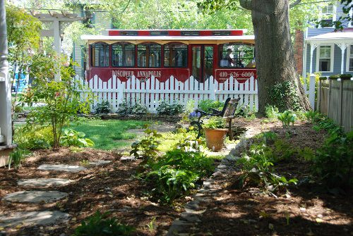 outdoor shot of shaded gardens with stone path, green plants, bench, tree trunk with ivy, picket fence, Discover Annapolis trolley, and corner of house on left side with small trees