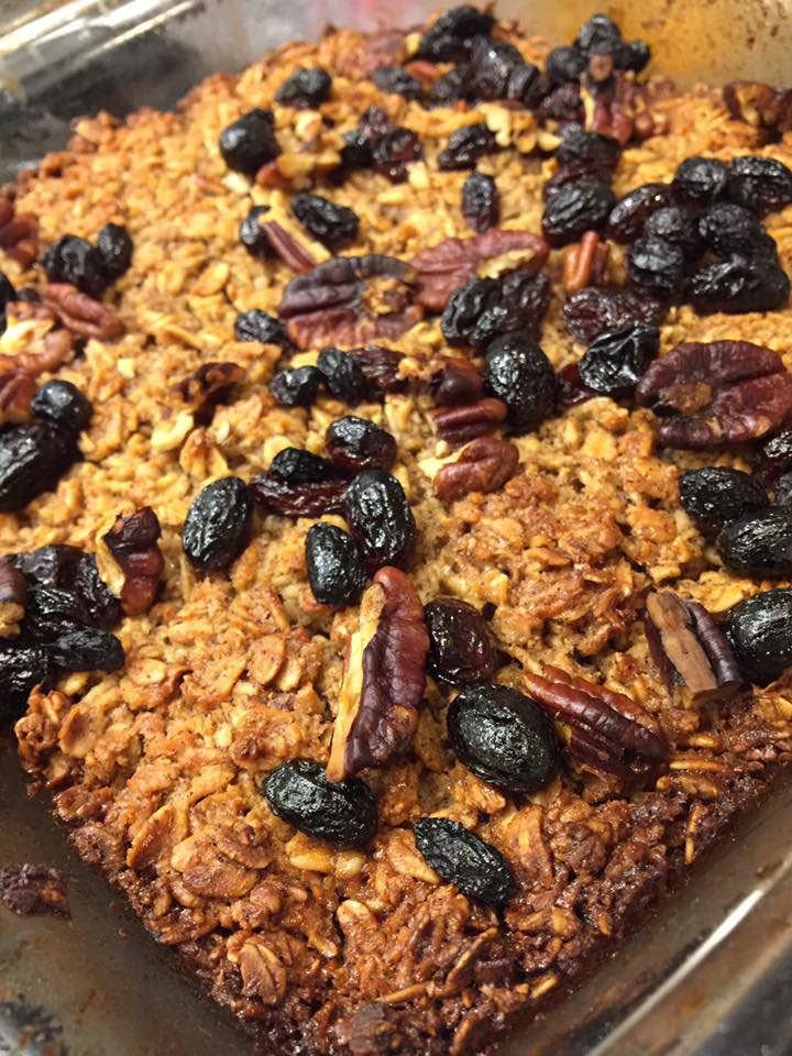close up of homemade baked oatmeal decorated with raisins, craisins and pecans