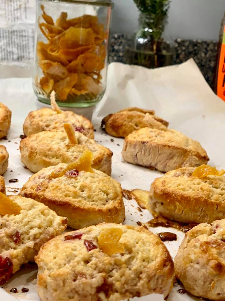 12 homemade orange and craisin scones on baking sheet with jar of homemade orange peels in the back as well as fresh rosemary in a vase and part of a recipe book