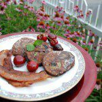 three homemade sourdough banana pancakes with a side of bacon decorated with cherries and powdered sugar on white and pink china plate with red charger against pink flowers with green stems and white picket fence